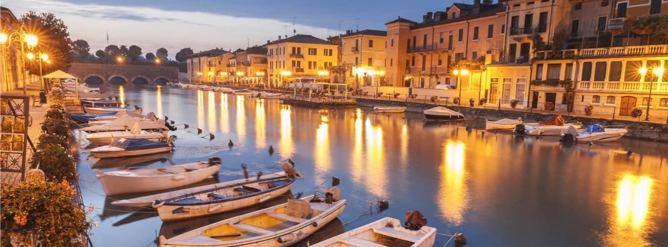 Italien Reiseziele - angelegte Boote am beleuchteten Gardasee